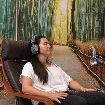 Woman sitting on a chair, wearing a headphone